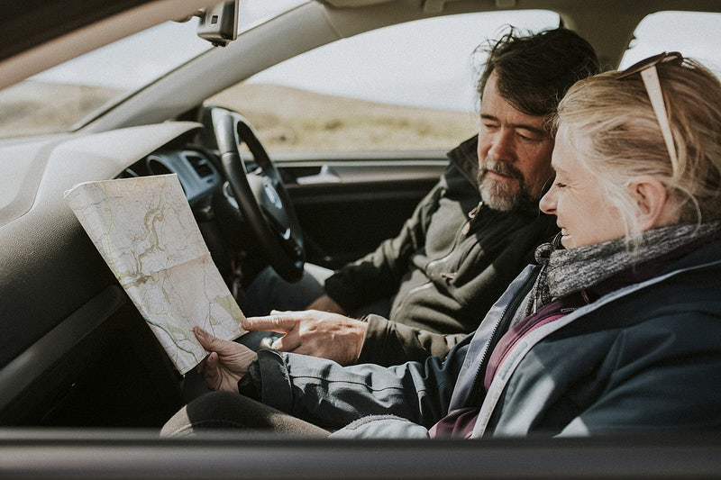 Senior tourist couple looking at the map in the car